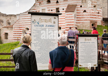 History of the Janowiec Castle, people reading the visitor information board in front of the bridge to historical - Stock Image