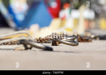 Nautical anchor chain with rust in the pier. - Stock Image