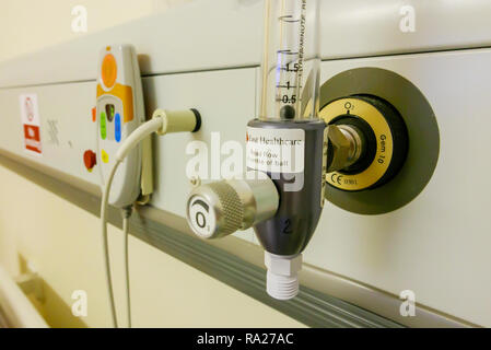 Bed head unit in a hospital ward showing an oxygen supply and a nurses call bell. - Stock Image