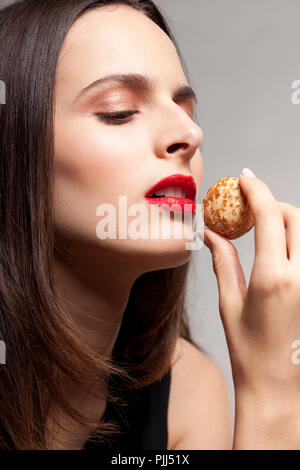 woman holding a cake with opened month - Stock Image