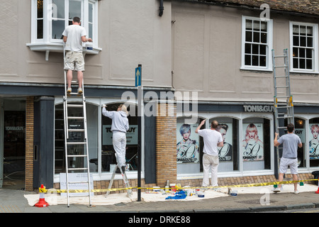 Team of painters, one on ladders, paint shop front, Cambridge, England - Stock Image