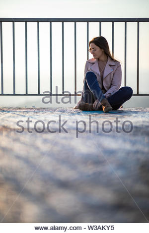 Beautiful woman portrait sitting on a viewpoint railing with blurred background and copy space - Stock Image