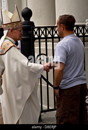 Former Archbishop shakes hands with man in fron of St. Louis Cathedral, New Orleans, USA - Stock Image