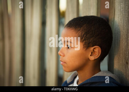 Lonely little boy outside on a brick wall. - Stock Image