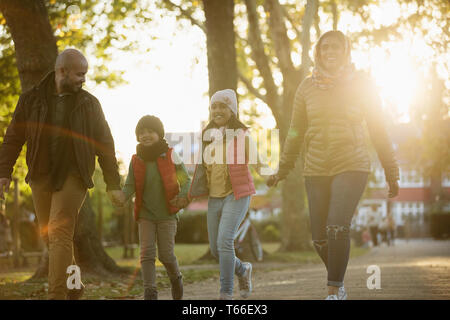 Happy family holding hands, walking in sunny autumn park - Stock Image