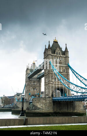 A plane flying over Tower Bridge in London. - Stock Image
