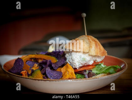 Tuna fish sandwich and colorful chips, in  a bowl over wooden table, viewed from the side, - Stock Image