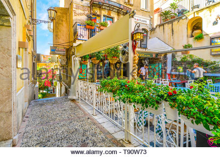 Restaurant workers prepare for the day at a colorful and picturesque cafe just off of Corso Umberto, the main street in Taormina Italy, Sicily - Stock Image