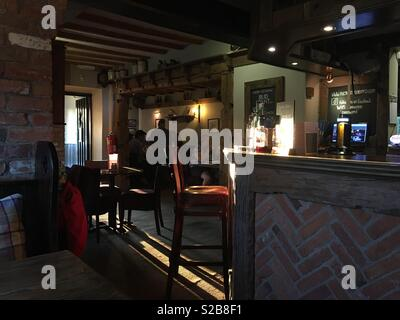 Interior of a country pub as light streams in through an open door. - Stock Image