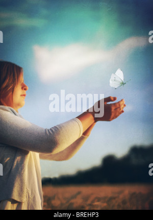 girl releasing butterfly - Stock Image