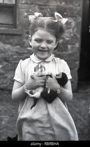 1950s, historical, young, happy girl with ribbons in her hair outside, holding in her hands two small puppies. - Stock Image