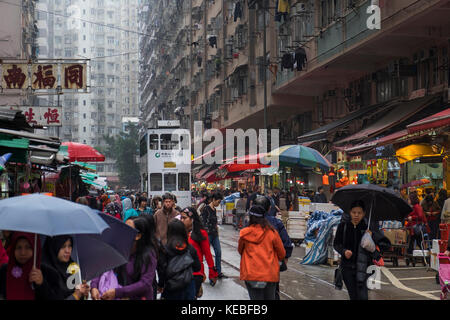 Tram passing through Chun Yeung Street market in North Point Hong Kong on a wet Sunday morning - Stock Image
