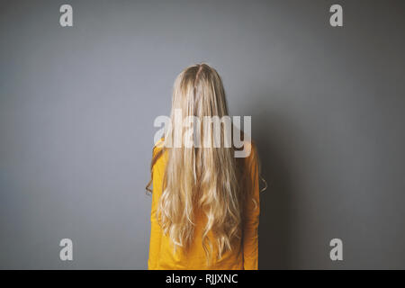 depressed young woman hiding her face behind long blond hair - shy or indifferent teenage girl - Stock Image