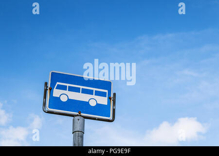 Bus stop sign against blue sky. - Stock Image