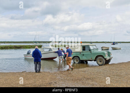 Small motor boat being uncoupled from a jeep and launched into the sea at Brancaster Staithe, North Norfolk, UK - Stock Image