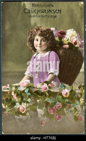 A greeting postcard printed in Germany, shows a girl with a basket of flowers. The inscription in German: Happy - Stock Image