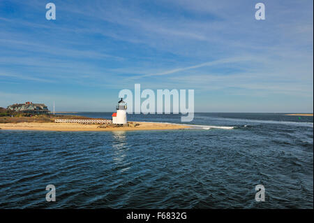 The Brant Point Lighthouse stands at the entrance to Nantucket Harbor a famous Cape Cod lighthouse welcoming visitors - Stock Image