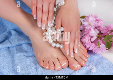 Woman bare feet and hands with french manicure and pedicure in spa salon on blue blue towel with decorative flower and pearls. Spa and recreation - Stock Image