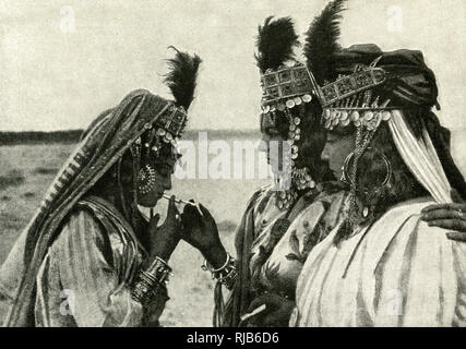 Three women of Algeria, North Africa, in jewelled costumes, lighting a cigarette. - Stock Image