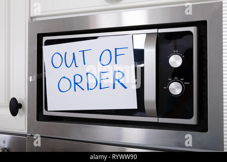 Written Text Out Of Order Message On Paper Over The Stuck Microwave Oven In Kitchen - Stock Image