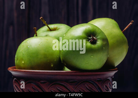 Ripe green apples close-up with dew in a bowl on a dark background - Stock Image