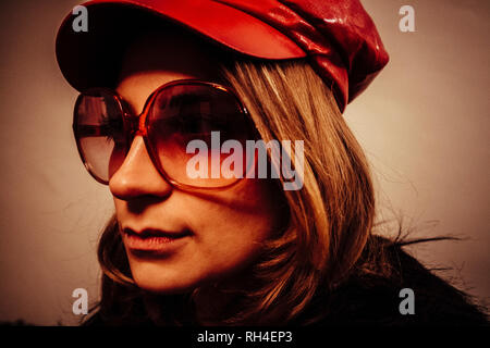 Close up portrait cool young woman wearing red leather cap and sunglasses - Stock Image