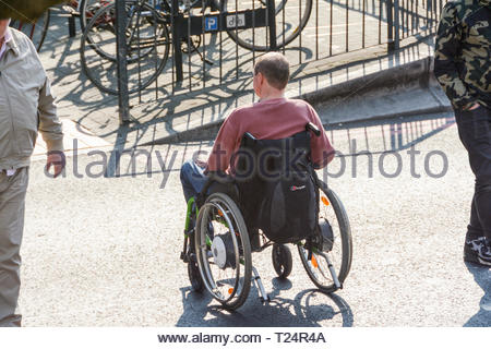 A disabled man in a wheelchair crossing the road in London, UK - Stock Image