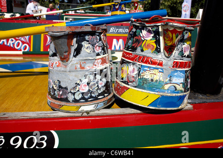 Traditional kettle and water jug decorated with roses and castles on the roof of working narrowboat Australia, moored - Stock Image