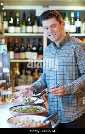 Portrait Of Male Customer In Delicatessen Filling Pot With Green Olives - Stock Image