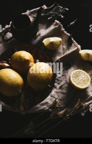 Still life of a tea cup, lemon slices and ginger on a rustic background, with copy space - Stock Image