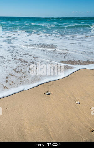 Incoming tide gently covering the sand on Fistral beach in Newquay in Cornwall. - Stock Image