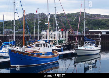 Sailing and pleasure boats moored in Lochinver harbour, Scotland, showing a refurbished timber boat in the foreground - Stock Image