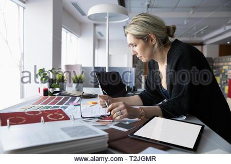 Female interior designer working in office - Stock Image