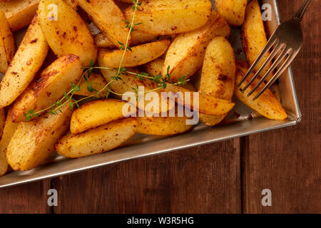 Potato wedges, oven roasted with thyme, close-up shot from above in a baking tray on a dark rustic wooden background - Stock Image