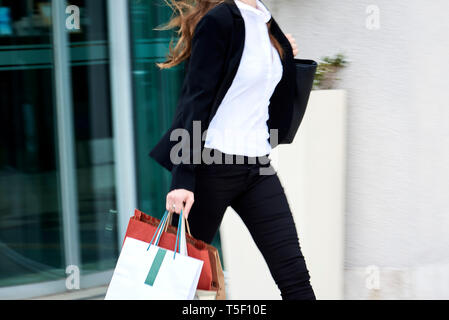 Young businesswoman walking on pavement - Stock Image