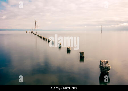 Long exposure of wooden pilings extending into the Salton Sea in California. - Stock Image