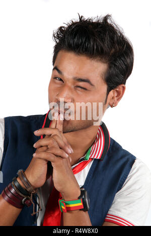 A young stylish Indian guy winking, on a white studio background - Stock Image