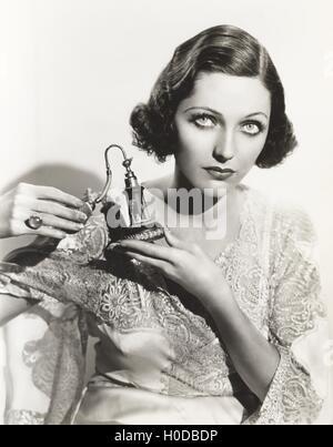 Woman holding perfume atomizer - Stock Image