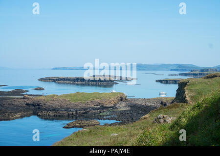 Harbour on Lunga, Treshnish Isles, from the clifftop. Small boats can be seen at anchor. - Stock Image