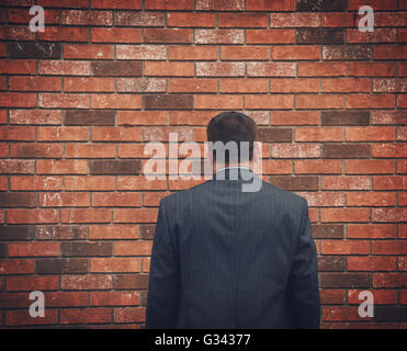 A business man has his back turned and looking at a brick wall. Can represent an obstacle, sadness or a struggle. - Stock Image