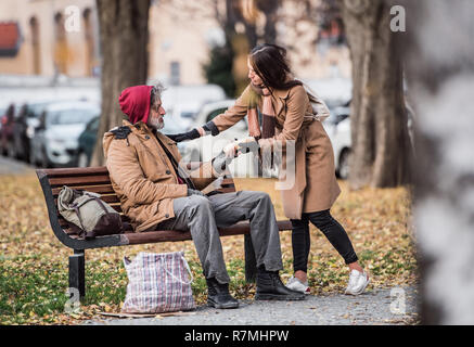 A young woman giving food to homeless beggar man sitting on a bench outdoors in city. - Stock Image