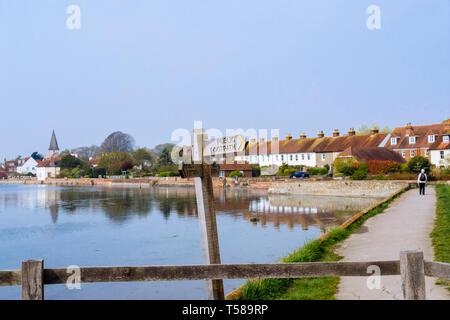 Public footpath signpost on path around Bosham Creek at high tide in Chichester harbour with village beyond. Bosham, West Sussex, England, UK - Stock Image