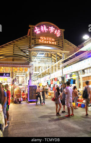 TAIPEI, TAIWAN - July 14, 2013: Crowd mingle at the entrance of Shilin Night Market in the Shilin District of Taipei. Shilin Market is the most popula - Stock Image