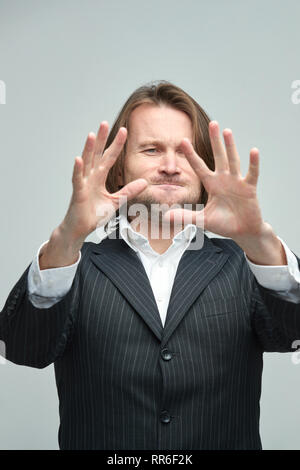 The handsome men in black suits on a white background, a white shirt, brutal man with long curly hairs, business man, very stylish, portrait, confiden - Stock Image