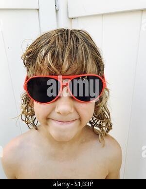 A young boy with sunglasses on looks at camera. - Stock Image