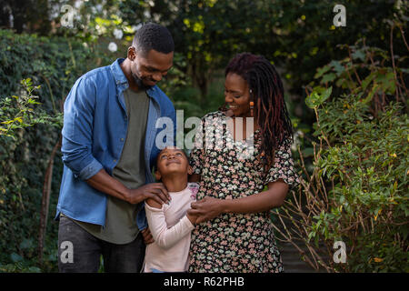 A mother, father and daughter looking at each other lovingly in a park - Stock Image