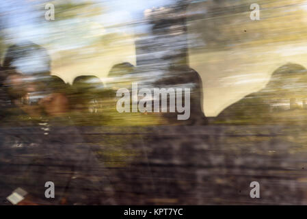 People sitting on a train with intentional motion blur of the speeding train - Stock Image