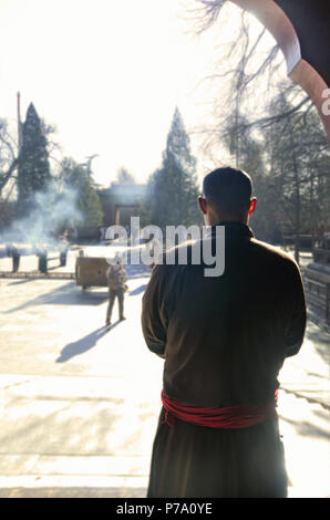 A young monk stares at Yonghe Temple courtyard, Beijing - Stock Image