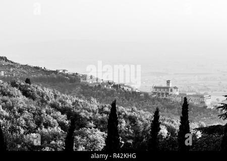 Beautiful view of Assisi town (Umbria) in autumn from an unusual place, behind an hill with trees. - Stock Image