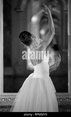 Beautiful ballerina dancing in front of the mirror. Black and white image. - Stock Image